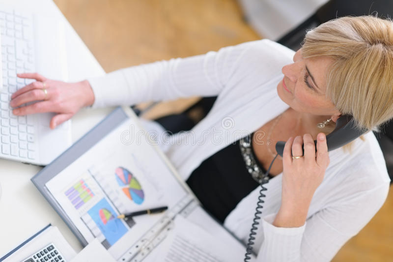 打电话的成熟的商业妇女。 顶视图 免版税库存照片