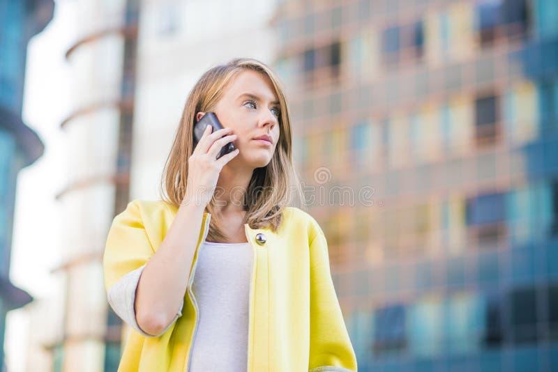 打电话的年轻女商人在她巧妙的电话 库存照片