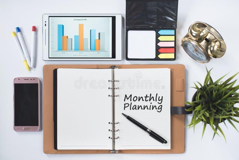 打电话, digita ltablet,公鸡,有月度计划词的空白的笔记本 图库摄影