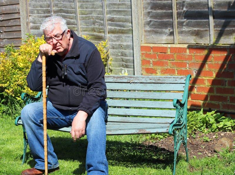 打盹在公园长椅的老人 免版税库存照片