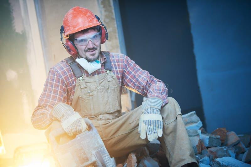 打破内墙 与爆破锤子的工作者画象 免版税图库摄影