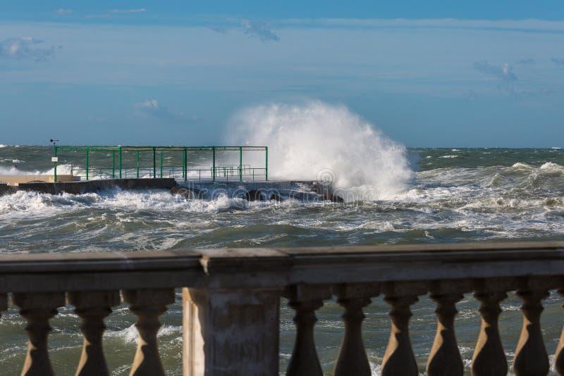 打破反对海滨散步的海波浪在大风天:多暴风雨的天气 库存图片