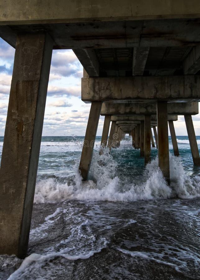 打破在一个具体码头下的海浪 库存图片