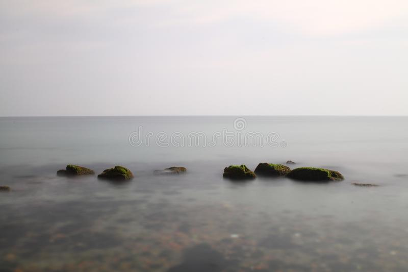 打破在岩石的海波浪 深蓝色海波浪击中了峭壁,被击中的岩石峭壁 打破在峭壁的强大海波浪,飞溅ove 免版税库存照片