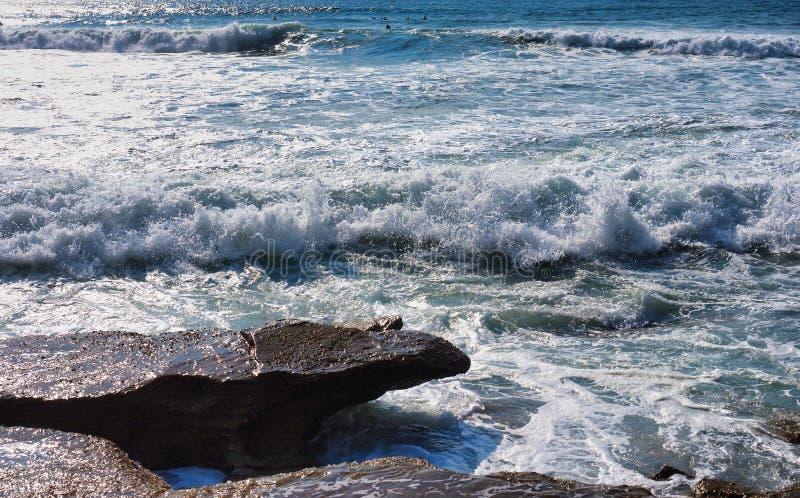 打破在岩石,悉尼,澳大利亚的打旋的太平洋波浪 免版税库存图片