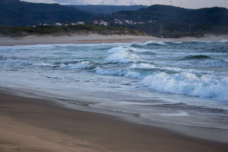 打破在平衡黄昏的含沙岸的起泡沫的海浪 在海滩与村庄和小山的海浪在背景 免版税库存图片