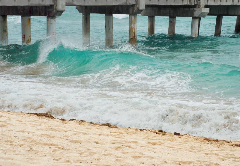 打破在海滩的Tourquoise波浪在有沙滩的一个码头旁边 免版税库存照片