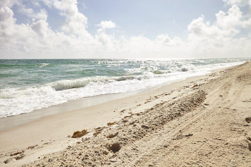 打破在空的桑迪西班牙海滩的海浪 库存照片