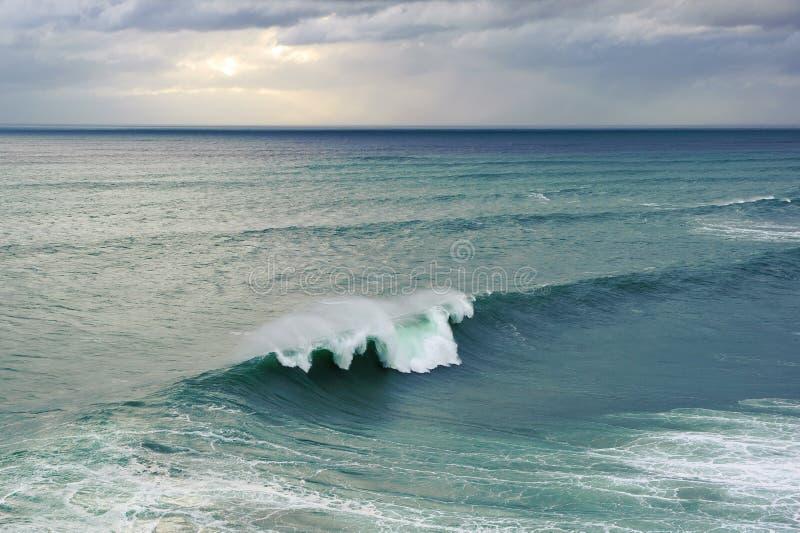 打破在Nazare,葡萄牙的巨大的海浪 免版税库存图片