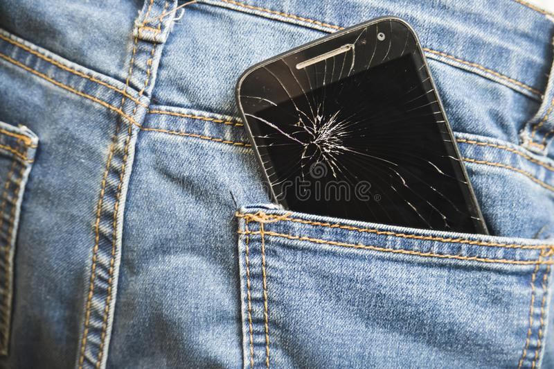 打破的手机崩裂了在牛仔裤在事故和粗心大意的概念的牛仔布长裤的后面口袋的触摸屏 库存图片
