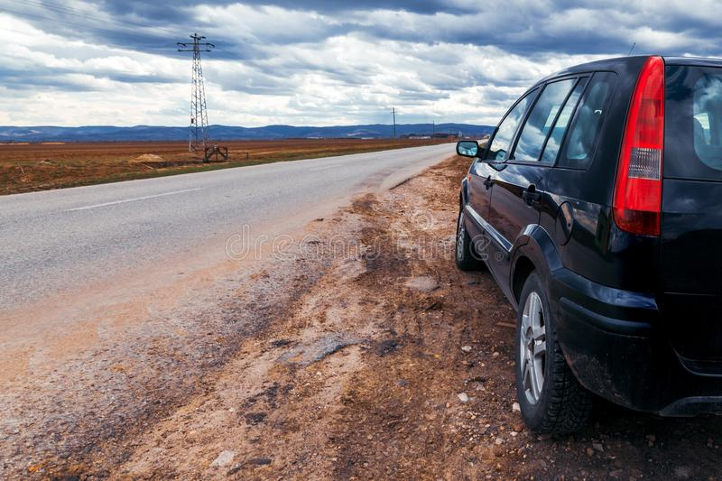 打破的汽车在风暴日路过路 库存图片