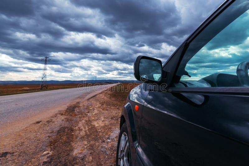 打破的汽车在风暴日路过路 免版税库存图片