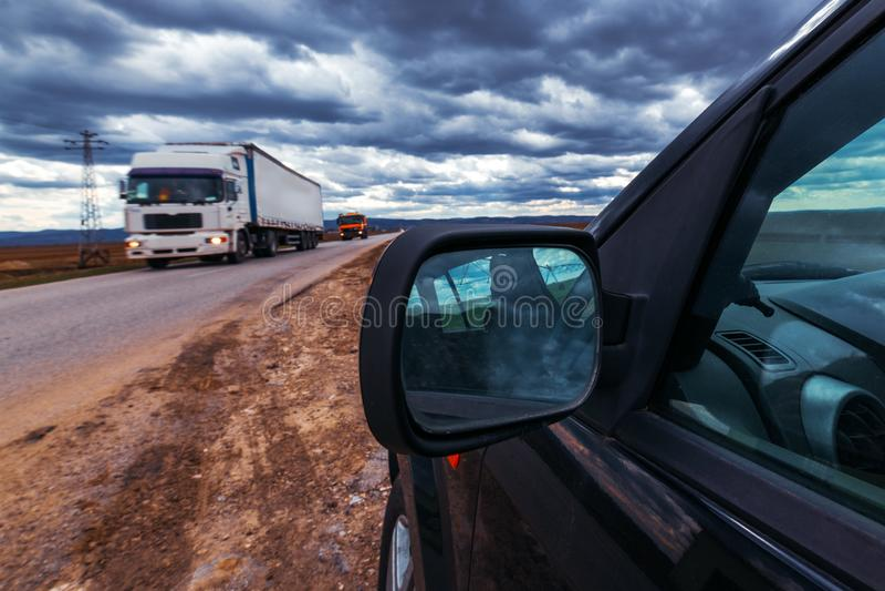 打破的汽车在风暴日路过路 库存照片