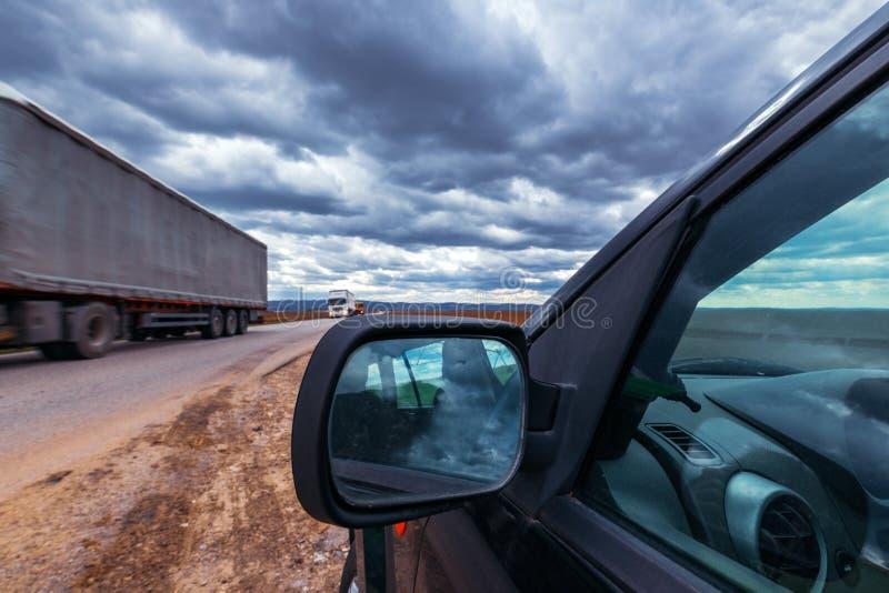 打破的汽车在风暴日路过路 免版税库存照片