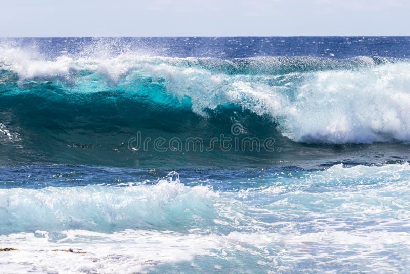 打破近海处在夏威夷的波浪;在前景的泡沫 蓝色海洋,天空,云彩在背景中 免版税库存图片