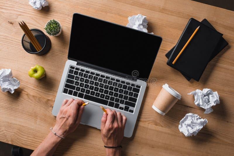 打破铅笔的商人播种的射击在有膝上型计算机的工作场所 免版税库存图片