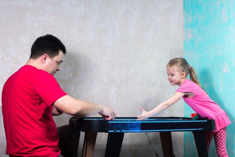 打空气曲棍球的爸爸和女儿 免版税库存图片