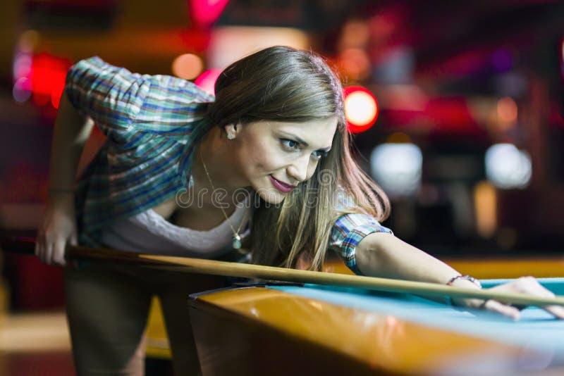 打算年轻美丽的小姐采取落袋撞球射击 免版税库存照片