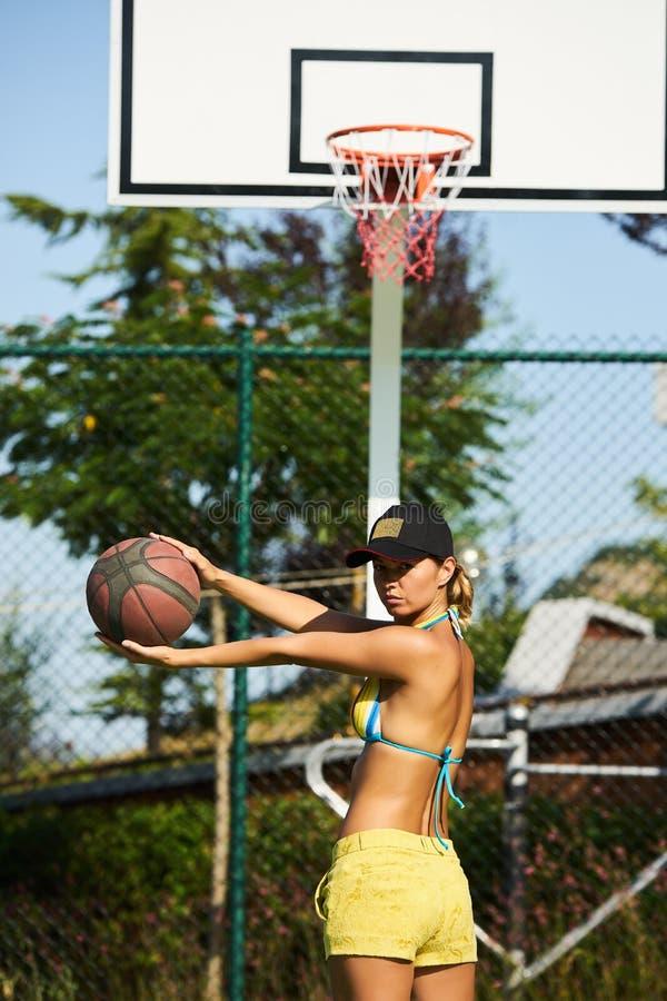 打篮球的美丽的少妇户外 免版税库存照片