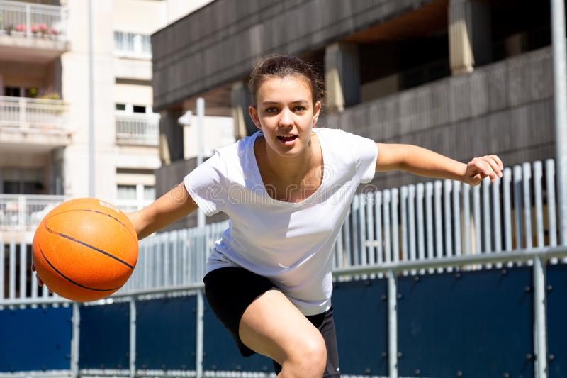 打篮球的青少年的女孩户外 免版税库存图片