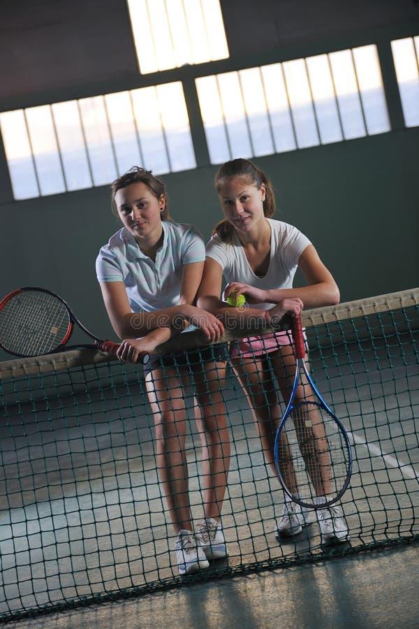 打网球比赛的女孩室内 免版税库存照片