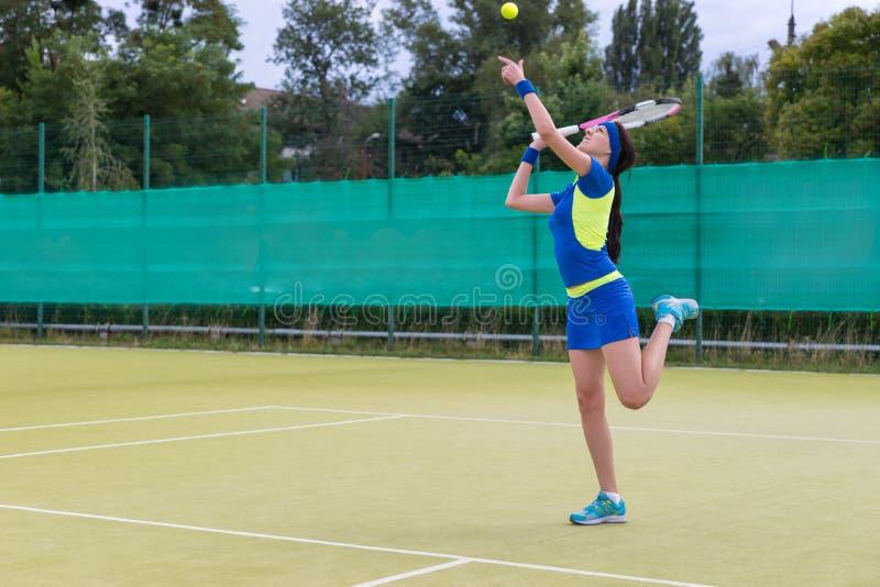 打网球的少妇佩带运动服服务网球b 图库摄影