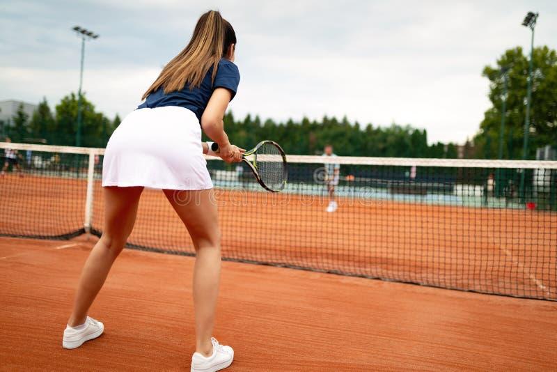 打网球的年轻愉快的妇女在网球场 库存图片