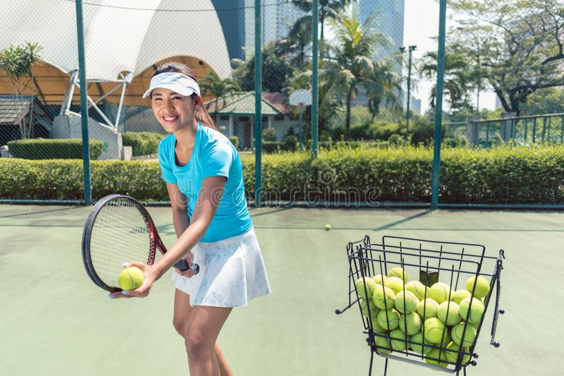 打网球的快乐的美丽的妇女在一个被开发的城市 图库摄影