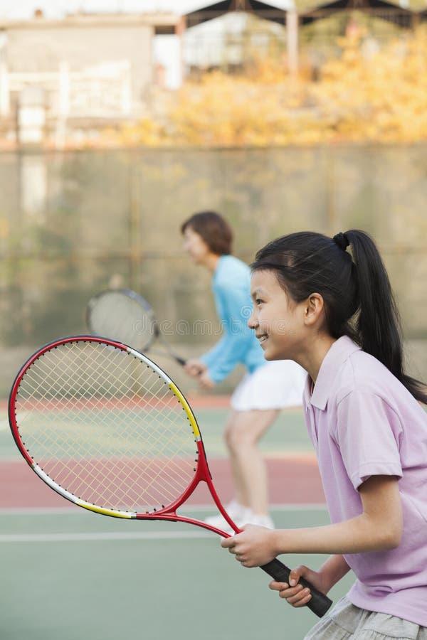打网球的母亲和女儿 免版税图库摄影