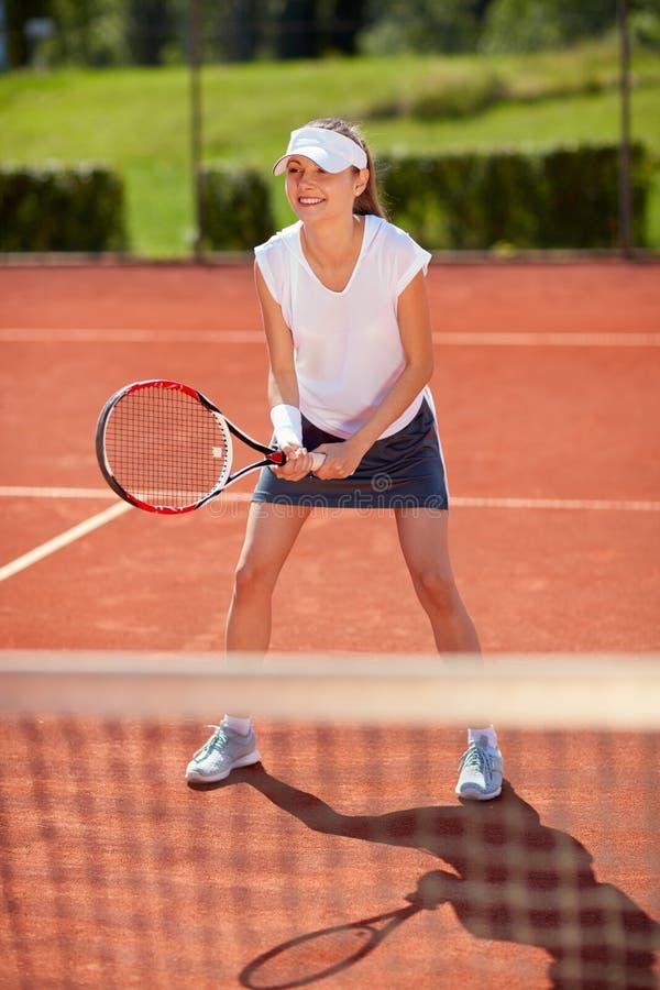 打网球的网球场的女孩 免版税库存图片