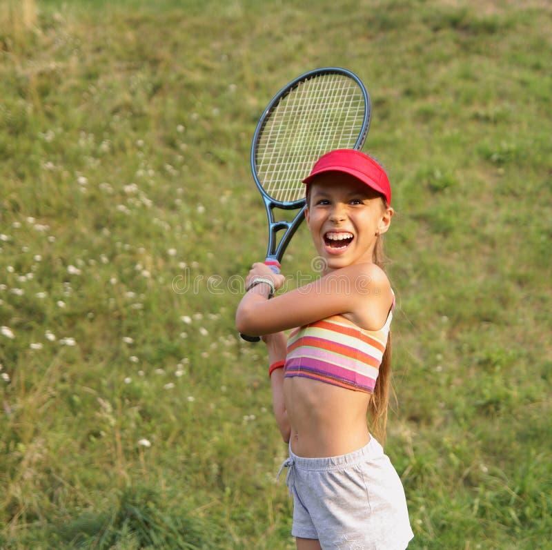 打网球的青春期前的女孩 免版税库存图片
