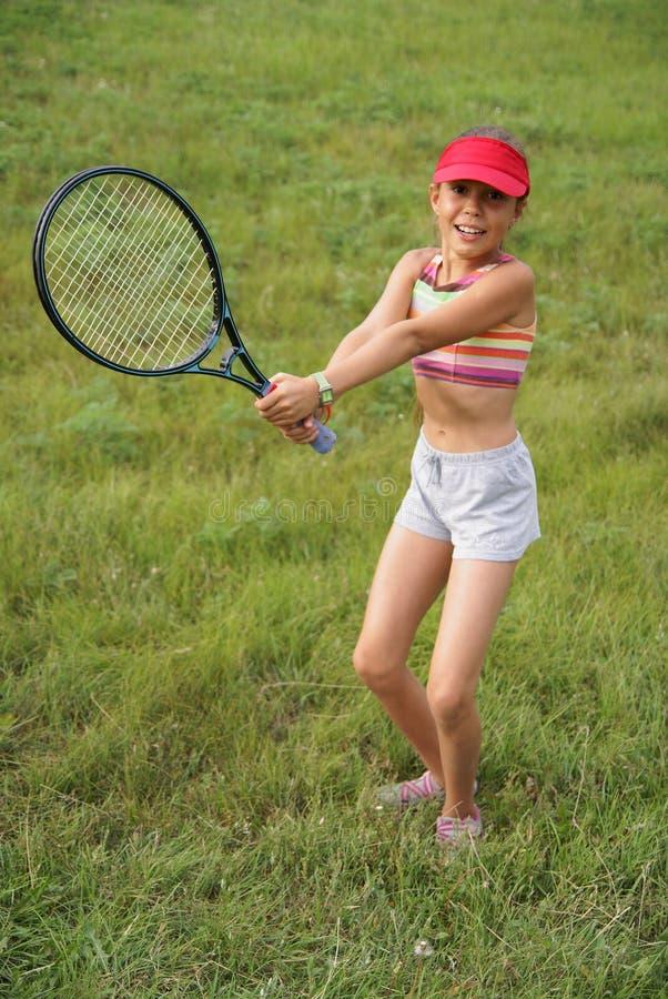 打网球的青春期前的女孩 免版税图库摄影