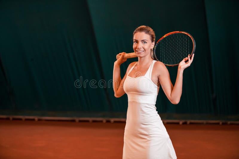 打网球的年轻女运动员 免版税库存图片