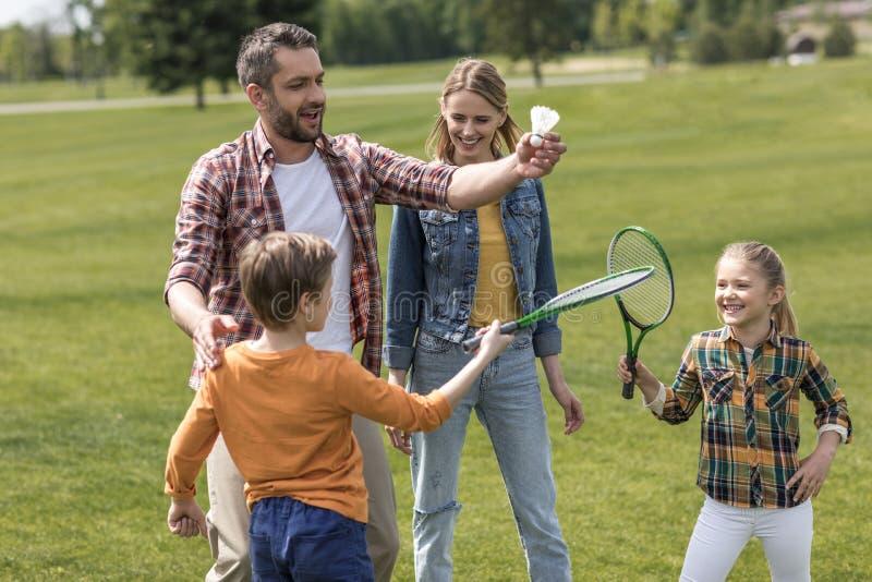 打羽毛球的偶然家庭在公园在白天 免版税库存照片