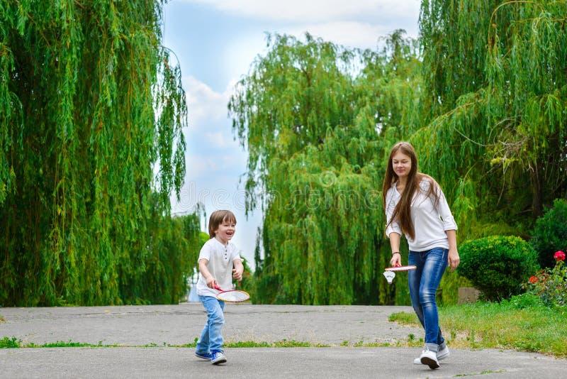 打羽毛球的女孩和男孩在公园 图库摄影
