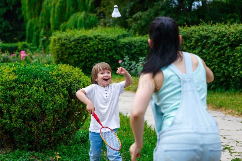 打羽毛球的母亲和儿子在公园 免版税库存照片
