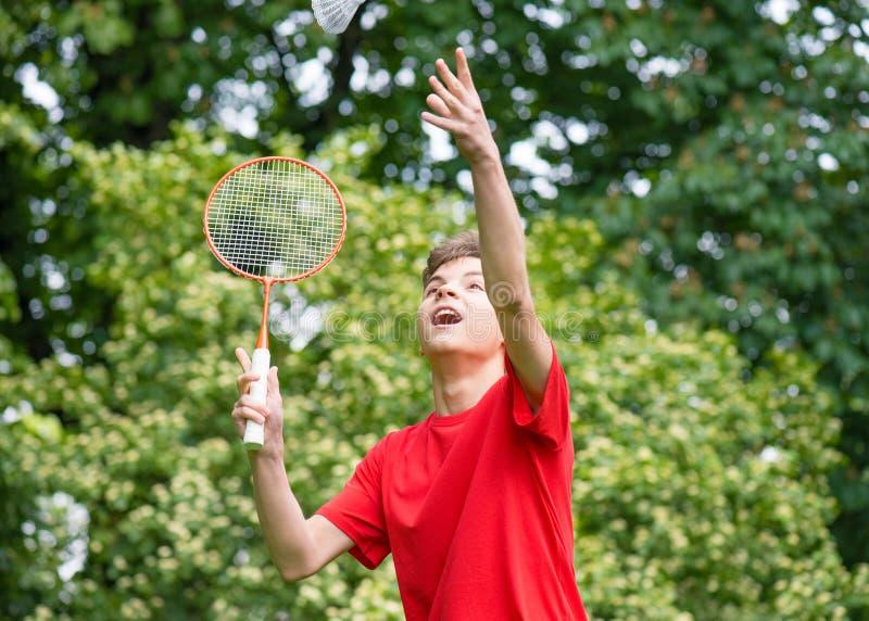 打羽毛球的青少年的男孩在公园 免版税库存图片