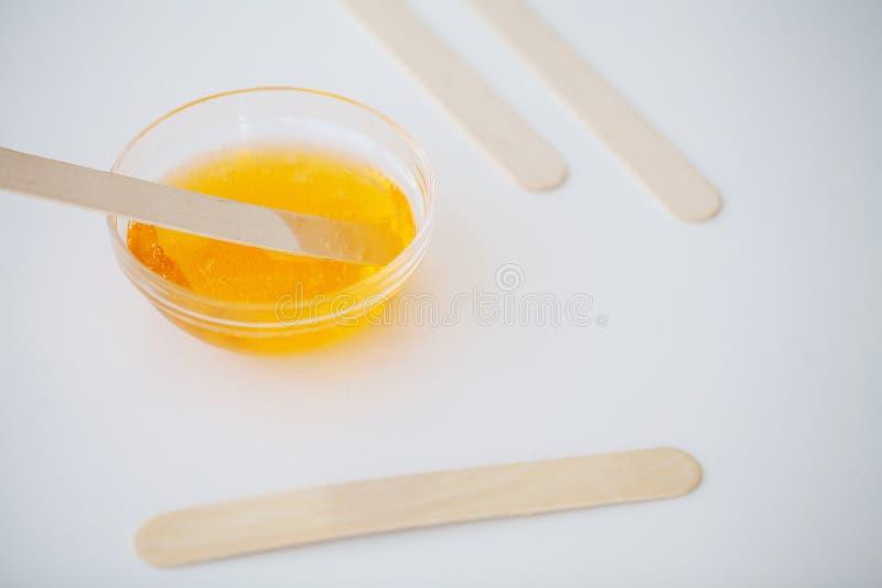 打蜡 加糖的浆糊在美容院 与蜡和棍子的概念去壳在白色背景顶视图 图库摄影