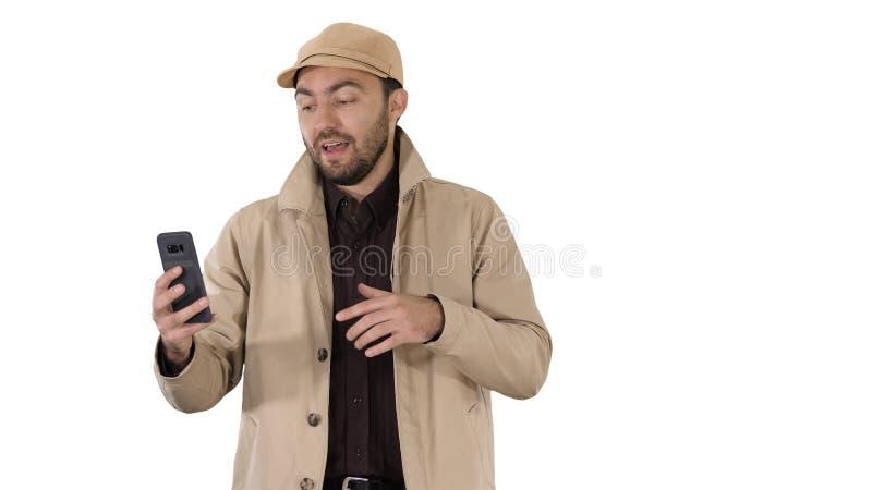 打视频通话的年轻人由他的手机,当走在白色背景时 图库摄影