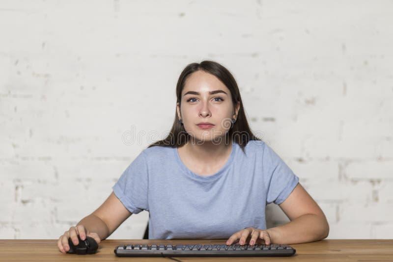 打计算机游戏的女孩 她小心地看起来平直,在她旁边有一只键盘和老鼠 免版税图库摄影