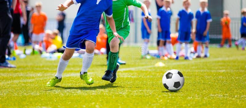 打足球赛的孩子 踢橄榄球足球的年轻男孩 库存图片
