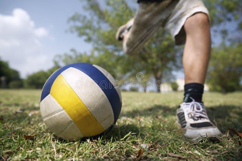 打足球赛,年轻男孩的孩子击中球在公园 库存照片