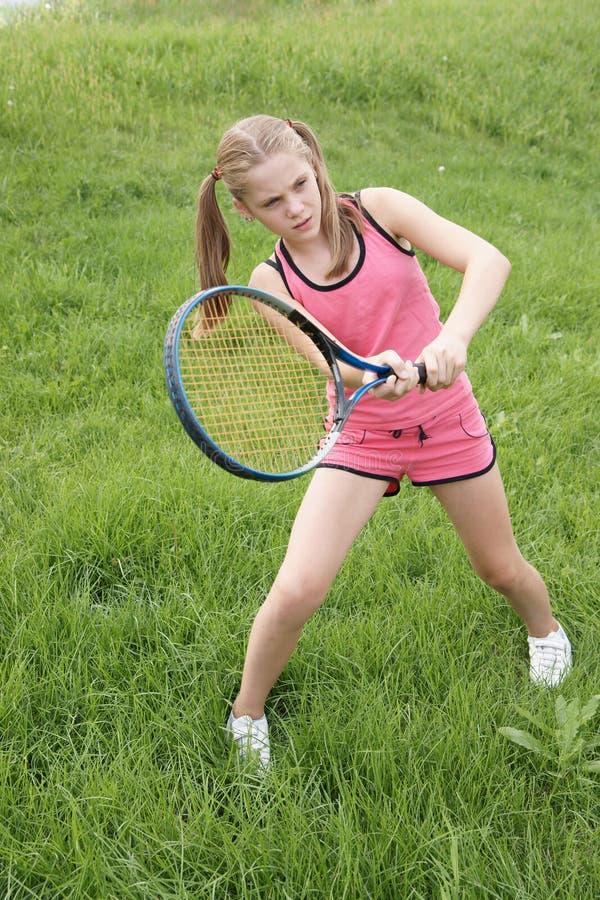 打青春期前的网球的女孩 免版税图库摄影