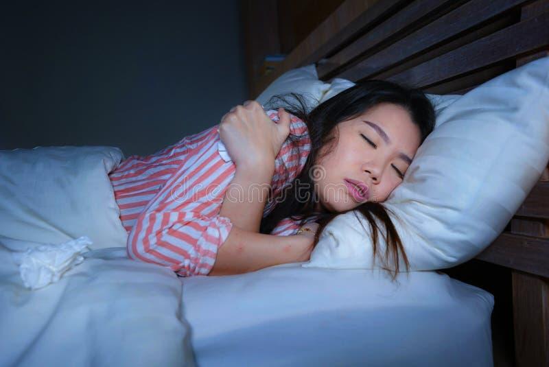 打颤在床遭受的寒冷和流感的年轻美丽的哀伤和沮丧的亚裔中国妇女在夜感觉不适在在附近  库存图片