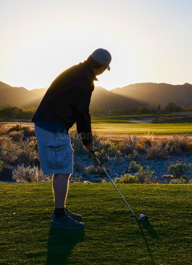 打高尔夫球作为暮色方法的人 库存图片