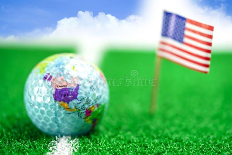 打高尔夫球地球与美国旗子的世界球在绿色草坪或领域 免版税库存照片