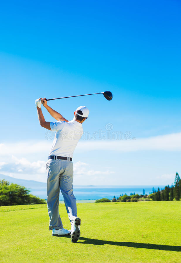 打高尔夫球的人,击中从发球区域的球 免版税库存图片
