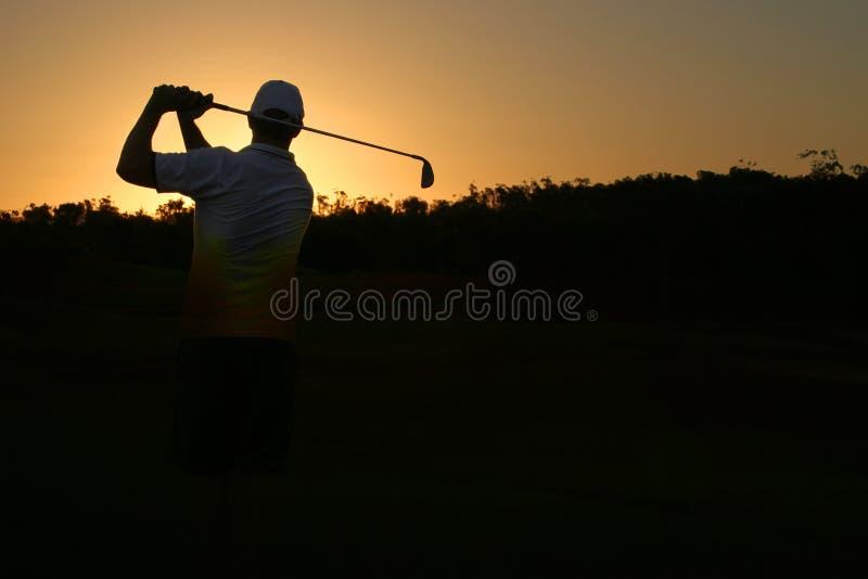 打高尔夫球的剪影 免版税库存照片