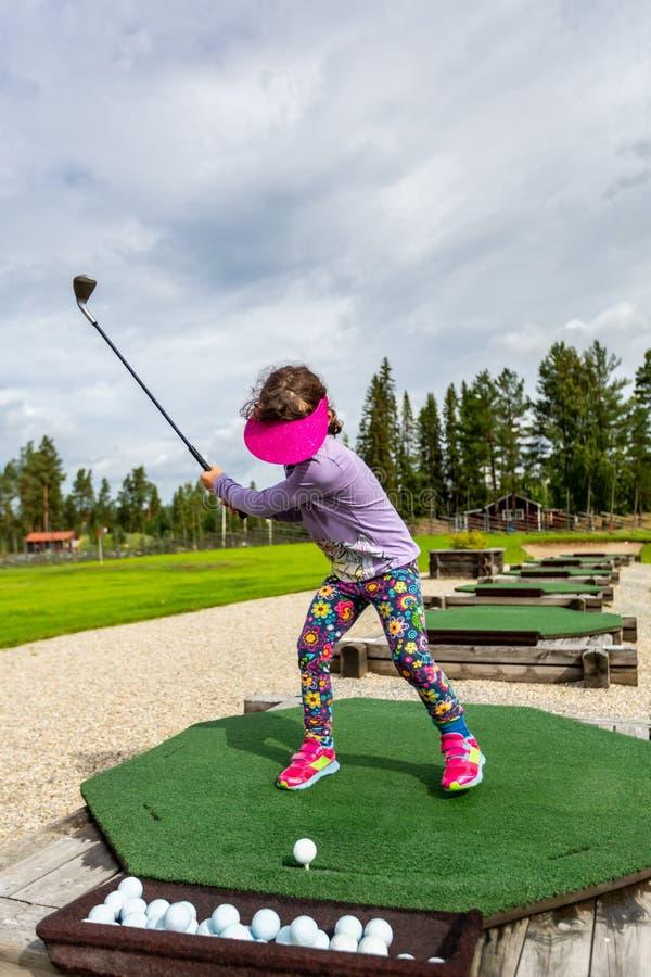 打高尔夫球的开车范围的少女户外和实践她的摇摆 免版税库存图片