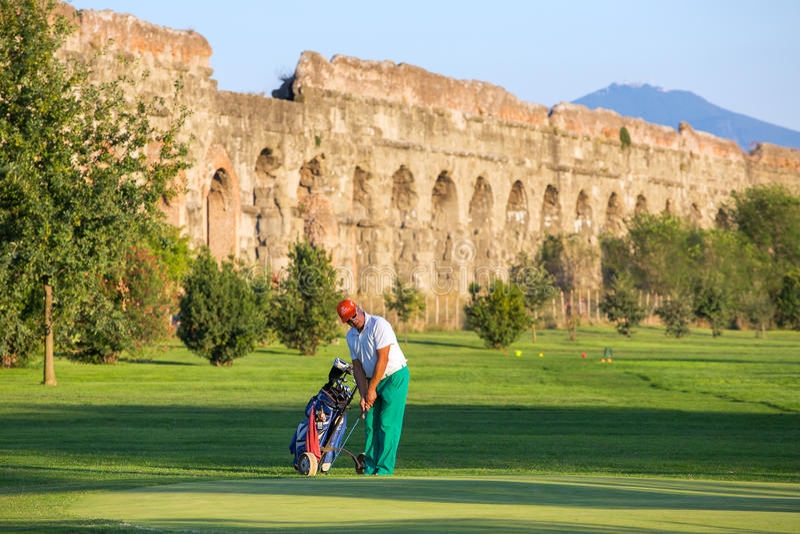打高尔夫球的未认出的人在高尔夫球场在古老罗马渡槽旁边 库存照片